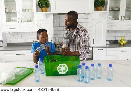 Happy african american father and son in kitchen talking and sorting plastic waste for recycling. family spending time at home.