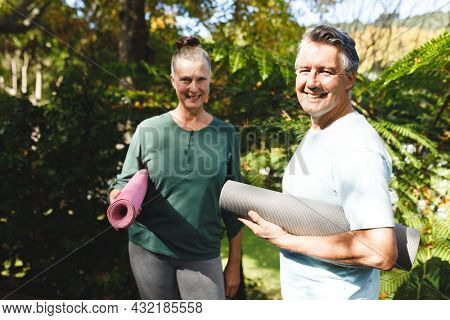 Portrait of happy senior caucasian couple holding yoga mats, looking to camera in sunny garden. healthy retirement lifestyle, spending time at home.