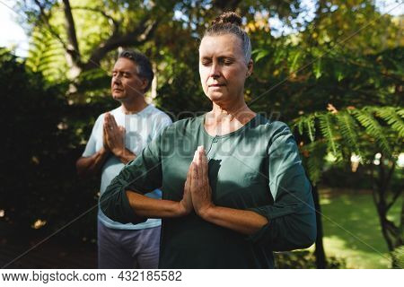 Happy senior caucasian couple practicing yoga, meditating in sunny garden. retirement healthy retirement lifestyle, spending time at home.