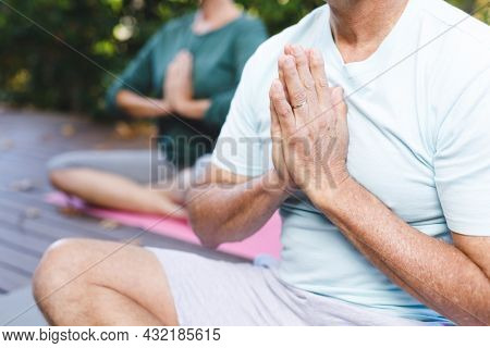 Midsection of senior caucasian couple practicing yoga, meditating in sunny garden. healthy retirement lifestyle, spending time at home.
