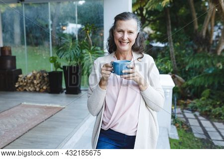 Portrait of happy senior caucasian woman looking to camera, holding cup in garden. retirement lifestyle, spending time alone at home.