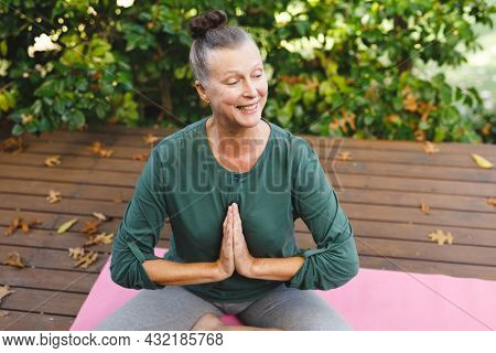 Happy senior caucasian woman practicing yoga, meditating in sunny garden. healthy retirement lifestyle, spending time at home.