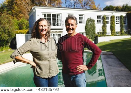 Portrait of happy senior caucasian couple embracing, looking to camera in sunny garden. luxury retirement lifestyle, spending time at home.