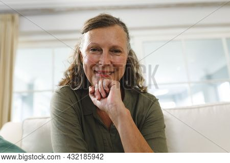 Senior caucasian woman in living room, sitting on sofa, making video call. retirement lifestyle, spending time at home with technology.