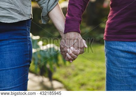 Midsection of senior caucasian couple holding hands walking in garden. retirement lifestyle, spending time at home.