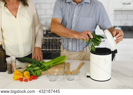 Midsection senior caucasian couple in modern kitchen, cooking together composting organic waste. retirement lifestyle, spending time at home.
