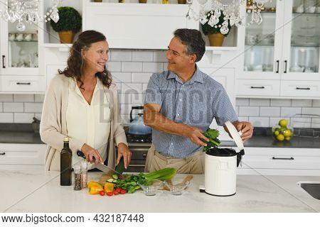 Happy senior caucasian couple in modern kitchen, cooking together composting organic waste. retirement lifestyle, spending time at home.