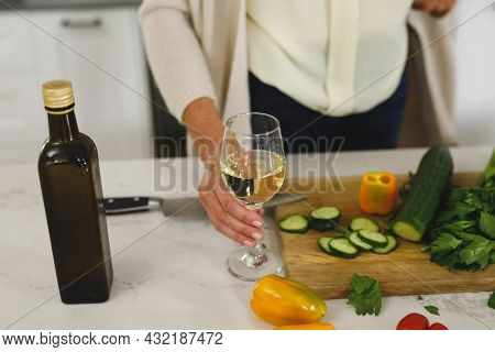 Midsection of senior caucasian woman in modern kitchen, holding glass of wine. retirement lifestyle, spending time at home.