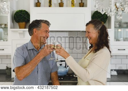 Happy senior caucasian couple in modern kitchen, drinking wine, making a toast and smiling. retirement lifestyle, spending time at home.