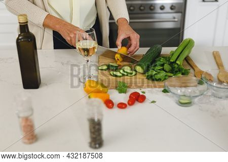 Midsection of senior caucasian woman in modern kitchen, chopping vegetables. retirement lifestyle, spending time at home.