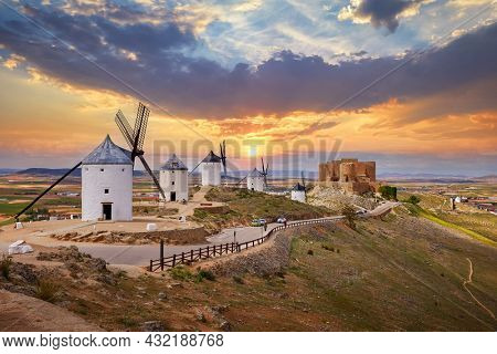 Wind mills and old castle in Consuegra, Toledo, Castilla La Mancha, Spain. Picturesque panorama landscape with road and view to ancient walls and windmills on blue sky with clouds.