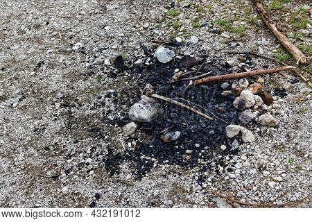 Burnt Charred Fireplace On A Gravel Parking Lot With Stones Under A Cloudy Sky During The Day Withou