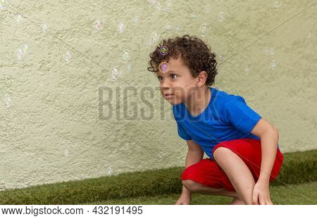 Curly-haired Boy With Freckles Playing In The Backyard With Soap Bubbles.