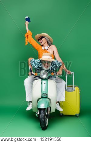Multiethnic And Cheerful Middle Aged Couple In Sun Hats Holding Passports With Air Tickets While Rid