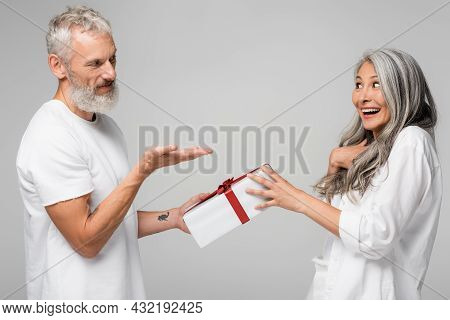 Happy Middle Aged Man Pointing With Hand At Amazed Asian Wife While Giving Wrapped Gift Box Isolated