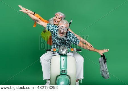 Multiethnic And Cheerful Middle Aged Couple With Outstretched Hands Riding Moped On Green