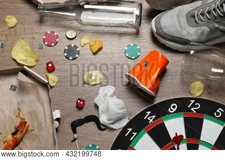 Food Leftovers, Shoes And Elements Of Different Games After Party On Wooden Floor, Flat Lay