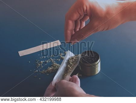 Close Up Man Hands Rolling A Joint With Herb Girder To Grind A Cannabis Buds On A Blue Background.ma