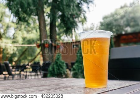 Light Wheat Beer In Plastic Glass On Wooden Table On Summer Terrace Of Tavern. Refreshing Drink. Sum