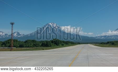 Yellow Lines Are Drawn On The Runway Of The Airfield. Ahead, Against The Background Of The Blue Sky,