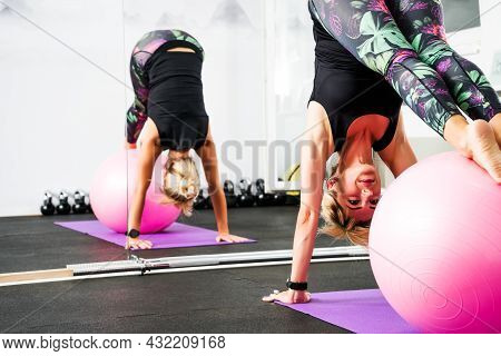 Adult Woman Is Practicing Pilates With Ball In Gym.