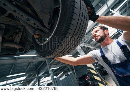 Auto Technician Detaching A Wheel From Car