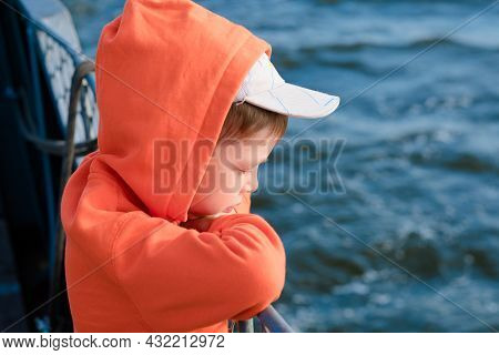The Boy On The Ferry Looks At The Sea. Ferry Travel. Portrait Of A Boy Against The Background Of The