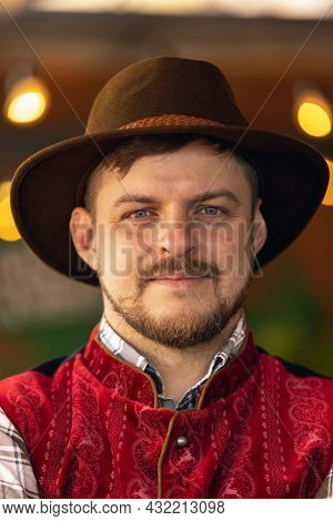 Close-up Portrait Of Caucasian Bearded Man Dressed In Traditional Bavarian Festive Costume, Hat And