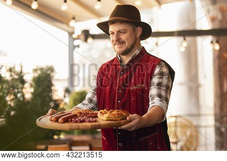 Happy Smiling Man, Waiter Dressed In Traditional Bavarian Costume Holding Round Wooden Tray With Fes