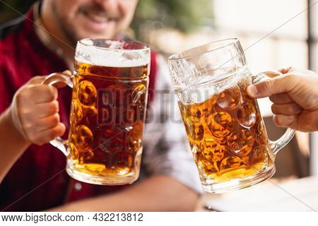 Close-up Two Mugs, Glasses Of Beer In Male Hands. Friends Meeting At Bar, Cafe Or Pub. Traditions, F