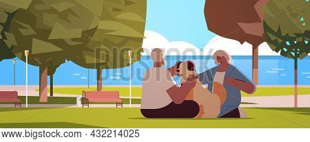 Senior Couple Spending Time With Dog In Urban Park Relaxation Retirement Concept