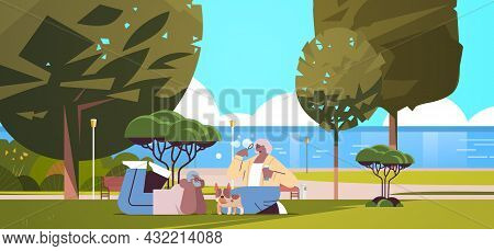 Senior Couple Blowing Bubbles And Spending Time With Dog In Urban Park Relaxation Retirement Concept