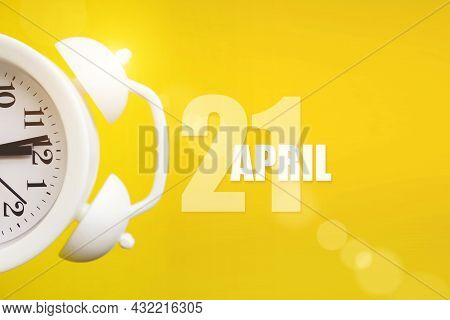 April 21st . Day 21 Of Month, Calendar Date. White Alarm Clock On Yellow Background With Calendar Da