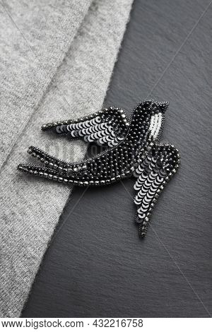 Seed Bead Embroidered Brooch In A Shape Of Black Swallow Bird On Gray And Black Background