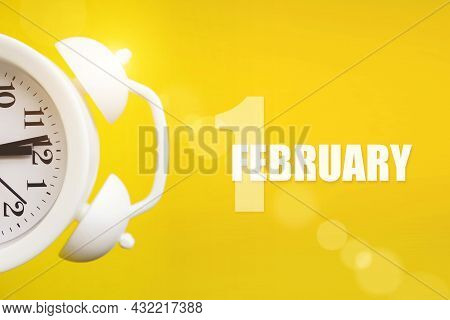 February 1st . Day 1 Of Month, Calendar Date. White Alarm Clock On Yellow Background With Calendar D