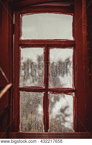 Red Wooden Window With Raindrops On The Glass. Old Shabby Window Frame