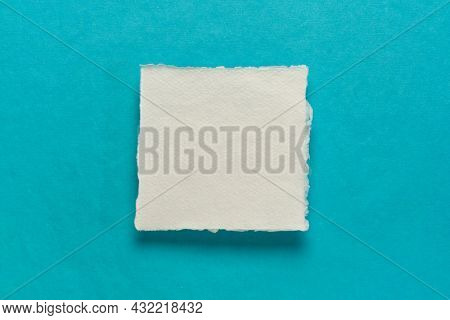 small square sheet of blank white Khadi paper against blue rag paper