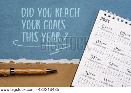 Did you reach your goals this year? Handwriting on a handmade paper with a pen and 2021 desktop calendar. Goal setting concept.