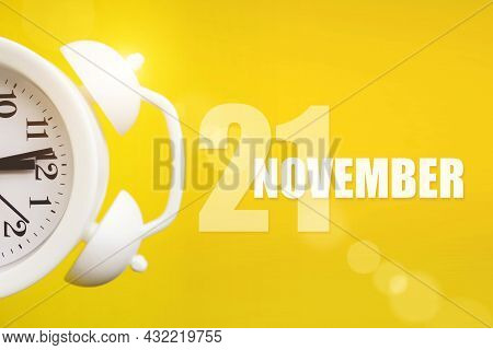 November 21st . Day 21 Of Month, Calendar Date. White Alarm Clock On Yellow Background With Calendar