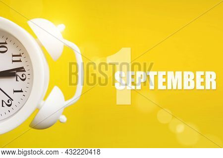 September 1st . Day 1 Of Month, Calendar Date. White Alarm Clock On Yellow Background With Calendar