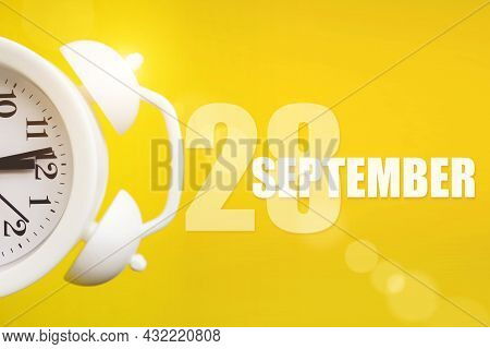 September 28th. Day 28 Of Month, Calendar Date. White Alarm Clock On Yellow Background With Calendar