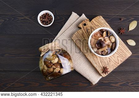 Pickled Mushrooms In A Glass Jar And Bowl On Dark Rustic Wooden Background. Marinated Mushrooms With