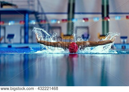 Professional Male Swimmer In Swimming Cap And Goggles In Motion And Action During Training At Pool,