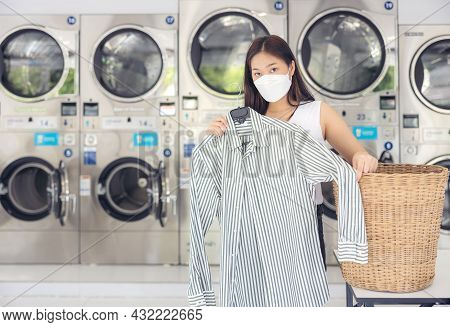 At A Laundromat Shop With Many Automatic Washing Machines, A Beautiful Woman Wearing A Mask Is Doing