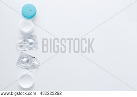 A Container For Lenses And Two Sealed Lenses Lie On The Side On A White Background With Space For Te