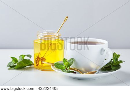 Black Tea In White Cup With Mint Leaves And Honey. Calming And Revitalizing Tea, Anti-stress And Rel