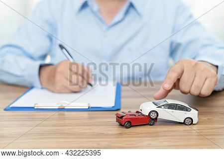 Car Insurance Concept : A Man Use A Pen Write Insurance Document On Table And Accident Toy Car Model