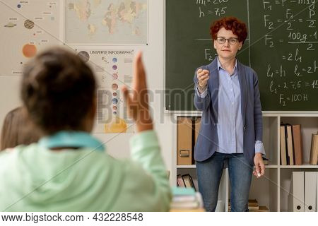 Young teacher standing by blackboard and pointing at one of schoolkids raising hand at lesson