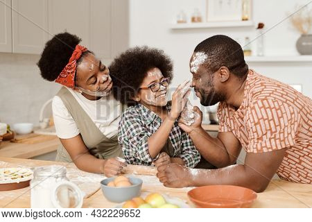 Cute little boy with floured hands touching face of his father by kitchen table
