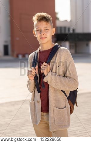 Secondary school pupil in casualwear standing against modern building outdoors